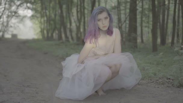 Krásná žena v bílých šatech a fialových vlasech se choují na zemi v lese a upravují vlasy. Video o smyslové kráse v pomalém pohybu-pohádkové scéně.