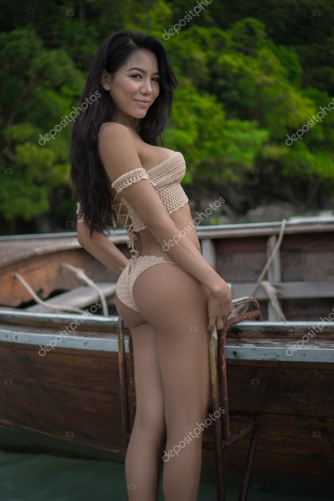 Asian beautiful smiling woman in crochet bikini on the boat. Sexy girl  standing on the boat ladder and looking into the camera - back view.– stock  image