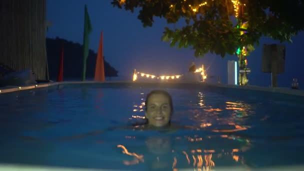 Boldog asszony pihentető a luxus medence mellett, az esti órákban. 4 k videót a nő, a medence mellett.