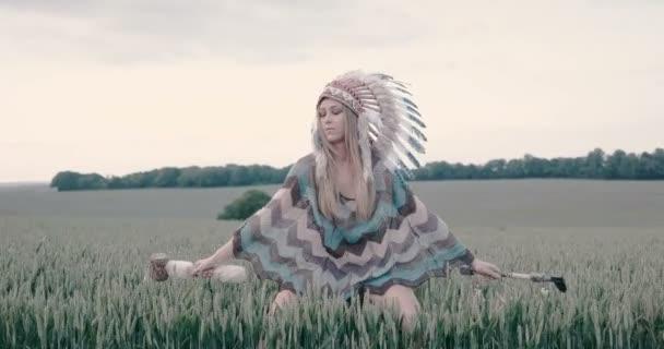 Indianisch aussehende schöne Frau mit Tomahawks auf dem Feld.