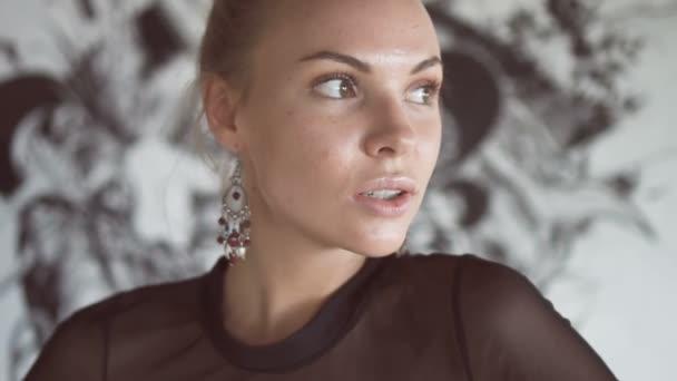 Detailní portrét sexy blond ženy nosit černé elegantní plavky a náušnice pózuje v opuštěné budově přes zeď s černobílý obraz pozadí - video zpomaleně