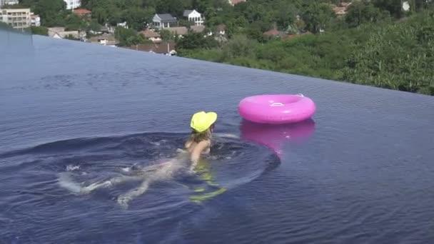 Hezká mladá žena nosí bikiny, žlutým kloboukem a fialové brýle plavání s růžové nafukovací kruh střešní bazén za slunečného dne nad zelenými stromy krajiny