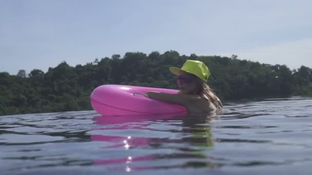 Pretty young woman wearing bikini, yellow hat and purple sunglasses swimming with pink inflatable ring in infinity rooftop pool on a sunny day over blue sky and green trees landscape.