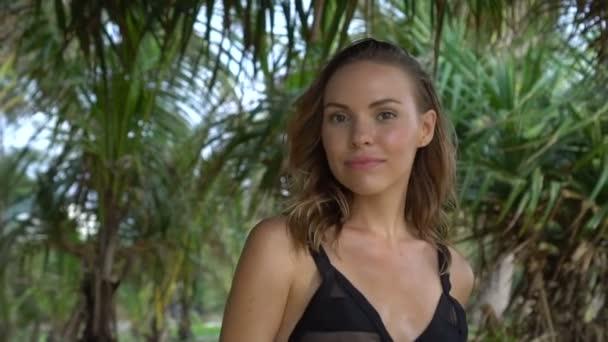 Nahaufnahme einer schönen blonden Glamour-Frau in schwarzer Badebekleidung, die lächelt und an einem schönen Sommertag zwischen Palmen in die Kamera schaut - Video in Zeitlupe