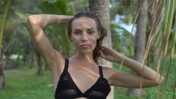 Closeup of beautiful blonde glamour woman wearing black swimwear posing on a beautiful summer day between palm trees - video in slow motion