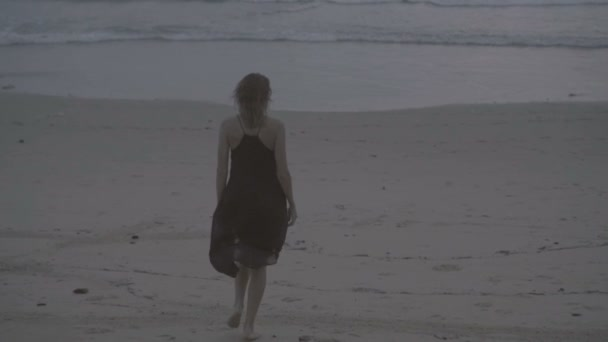 Back view of beautiful blonde glamour woman wearing black dress walking on a beach in a late summer afternoon with wet hair over sea and sky background - video in slow motion