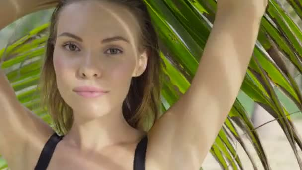Closeup of beautiful blonde glamour woman wearing black swimwear posing on a beautiful summer day between palm trees