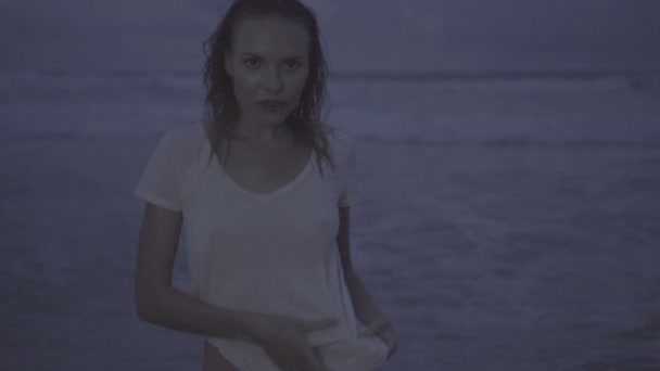Beautiful blonde sexy woman wearing t-shirt posing on a beach during summer evening with wet hair - video in slow motion