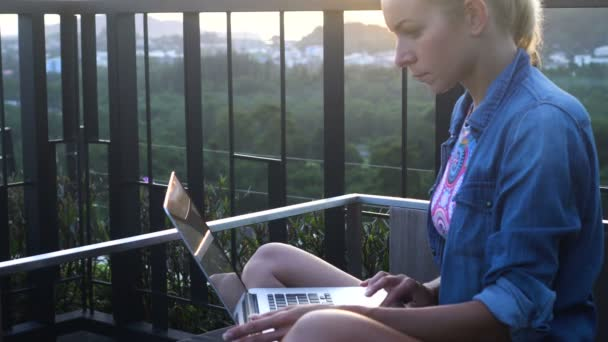 Side view of pretty blonde woman in bikini bra and jeans shirt working on a  laptop computer while sitting and enjoying early morning with birds  chirping and singing on a rooftop over beautiful