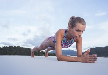 Bottom side view of pony tailed pretty blonde woman wearing colourful bikini doing plank push up exercise on a rooftop over blue sky and green mountains tops. Sport and healthy lifestyle concept