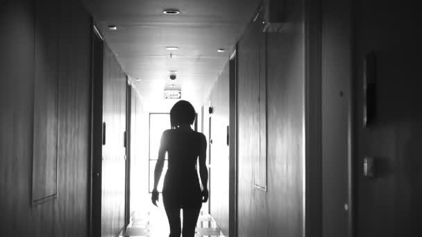Zadní pohled na krásné mladé ženy v hale na sobě elegantní šaty a náušnice - černé a bílé video