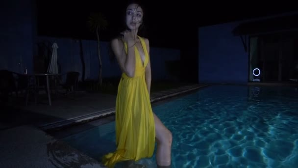 Gorgeous fashion woman with dark hair in elegant yellow dress smiling and posing beside swimming pool at luxurious villa at night