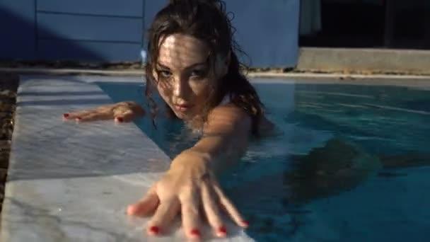 Detailní portrét krásné smyslné bruneta žena pózuje v venkovního bazénu během slunečného letního dne s stín čistý odraz na obličej a tělo