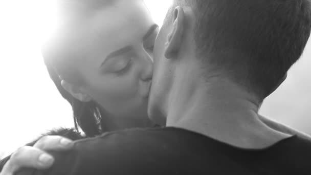 Černá a bílá detail videa Romantický polibek mezi pár přes pozadí oblohy