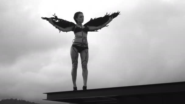 Černá a bílá video z krásné svůdné angel ženy nosit prádlo a koženými pásy, stojící na střeše s větrem v její křídla nad zamračená obloha