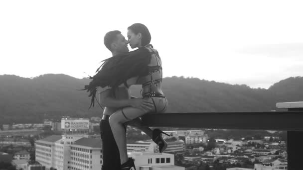 Mann küsst mit sinnlicher schwarzer Engelsfrau auf dem Dach