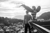Fotografie Black and white photo of romantic scene with shirtless man and sensual angel woman wearing lingerie, leather belts and high heels on the rooftop over sky and city landscape background