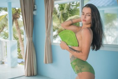 Beautiful young sexy topless brunette holding green folding hand fan and looking into the camera while kneeling on bed over blurred palm trees window view background