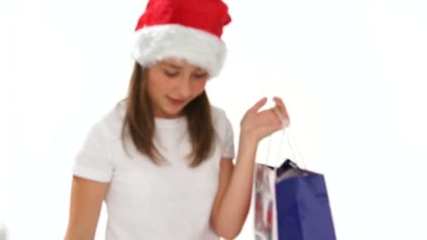aranyos kislány egy santa kalap átölelve egy mackó
