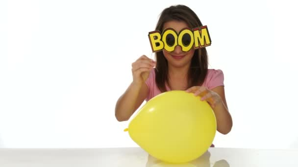 Young girl getting ready to burst a party balloon