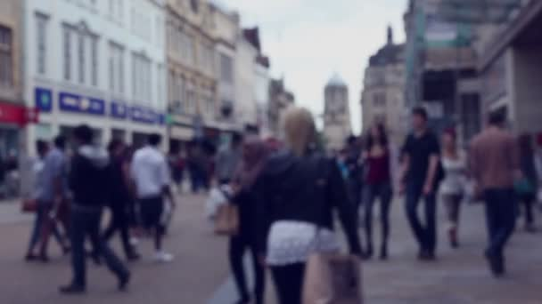 Blurred street scene with crowds of shoppers