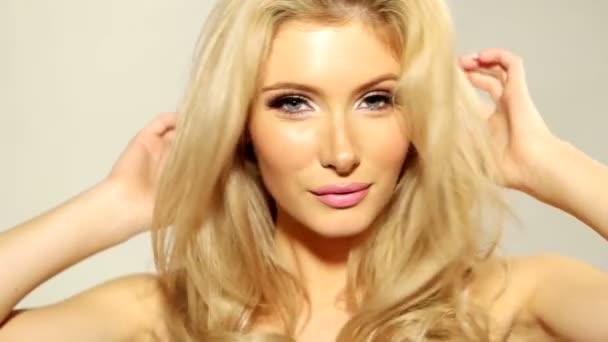 Zblízka šťastné Blond Girl dotýká její vlasy