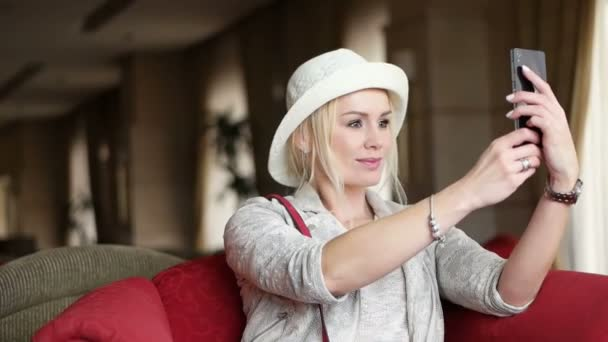 Woman taking self portrait in hotel sharing photos social media from holiday wearing hat