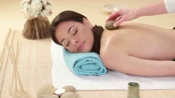 Woman getting back massage in the spa with lava stones