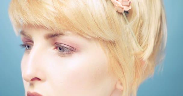 Krása ženy na modrém pozadí s květinou