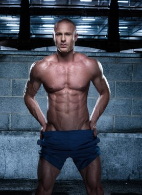 Sexy Bald Young Man Standing in a Rustic Building