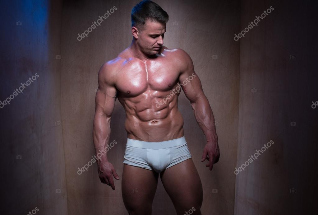 Muscular Man in White Boxer Shorts Looking Down