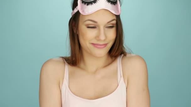 Atraktivní mladá žena, pózování a usmívá se v růžové spánku masku