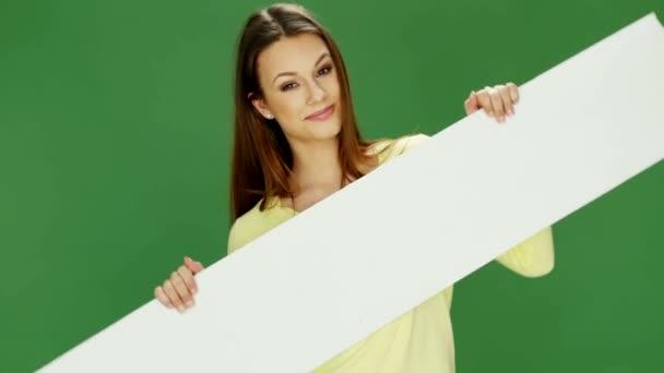 attraktive junge Frau mit weißem Banner auf grünem Hintergrund