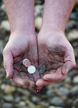 Dirty cupped hands holding few coins