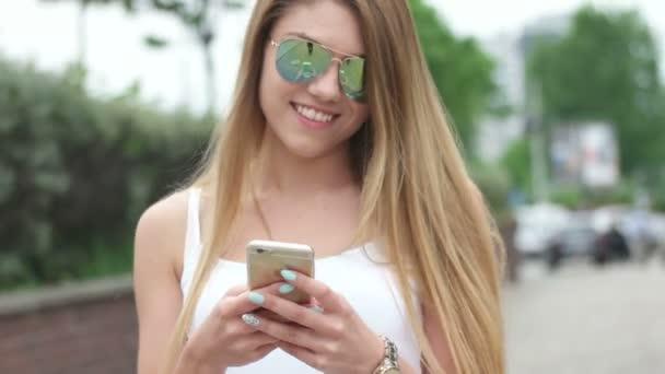 junge Frau schreibt SMS, verschickt SMS auf Smartphone