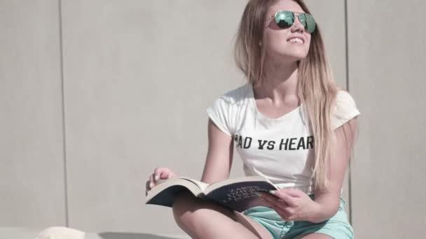 žena čte knihu na lavičce úsměvem šťastný na kameru