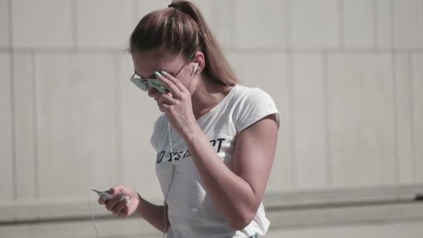 attraktive junge Frau mit Sonnenbrille, die in der Stadt Musik hört