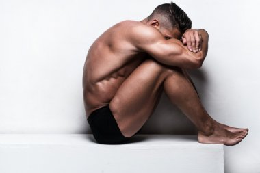 Muscular Man Sitting with Face Hidden Folded Arms