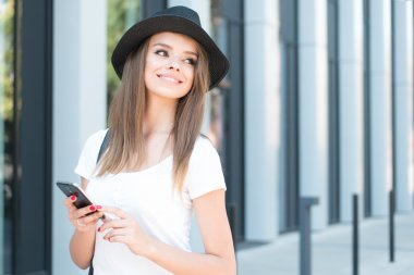 Attractive Woman with Phone Smiling into Distance