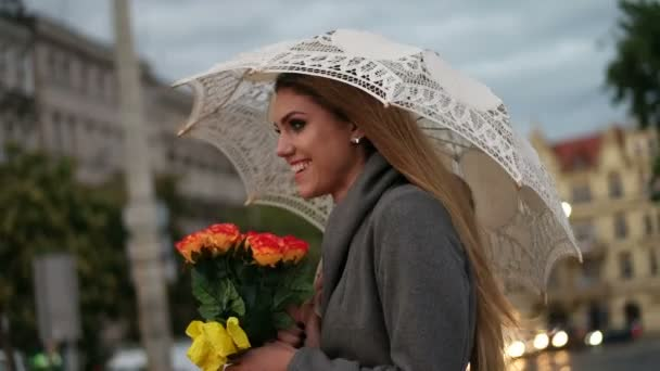 blonde woman holding a bunch of roses in a rainy day