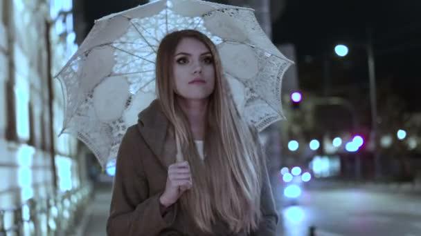 szőke nő gazdaság egy csomó rózsák, egy esős napon az esti órákban séta az esernyő