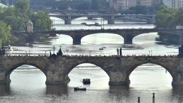Prague bridges across the Vltava river in Prague.Tourists walk across the Charles Bridge as transit flows across some of the other bridges on the Vltava river in beautiful Prague, Czechia.