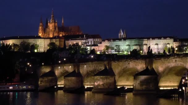 Karlův most, katedrála sv. Víta a Pražský hrad. Turistická loď pluje v noci pod Karlův most s katedrálou sv. Víta a Pražským hradem v pozadí.