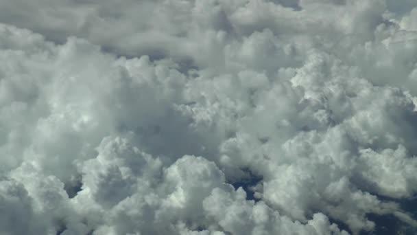 Létání nad mraky v komerčním letadle. Záběry z velké výšky. Fotoaparát hladce sleduje přirozený pohyb letadla ve vzduchu pro přidání realismu.