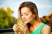 Mladá žena pít zelený čaj venku
