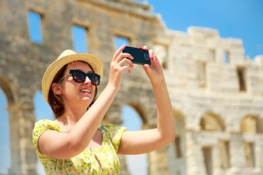 Woman Taking Photo of Arena with Smartphone