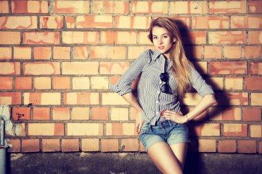 Trendy Fashion Girl at the Brick Wall