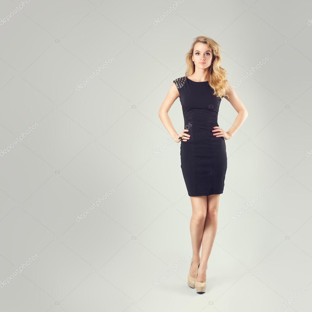 Красива жінка в чорне плаття з руки на стегна– стокове зображення e1ac9a8d075a5