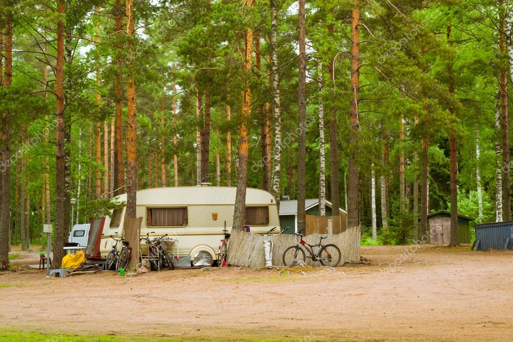 Camping vans and bikes in wooded campsite. Hamina, Finland, Suomi