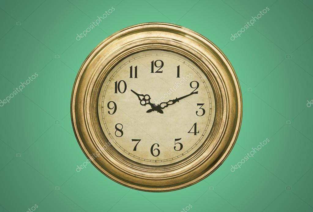 Rustic clock isolated over the green background